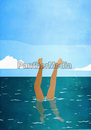 woman doing handstand underwater in ocean