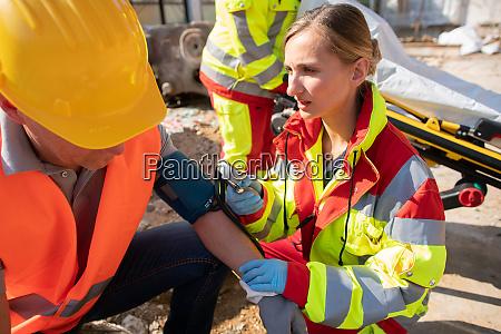 paramedic measuring blood pressure and talking