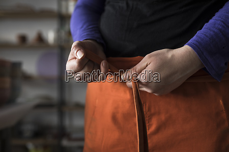 womans hands tying apron