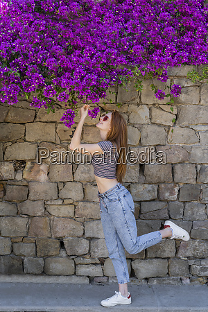 smiling woman smelling purple flowers