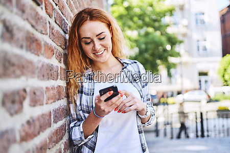 young woman leaning against brick wall