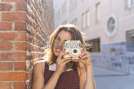 young woman leaning on brick wall