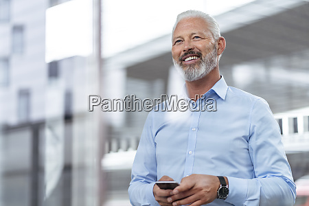 smiling mature businessman holding cell phone