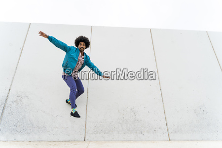 young hipster sliding on a white