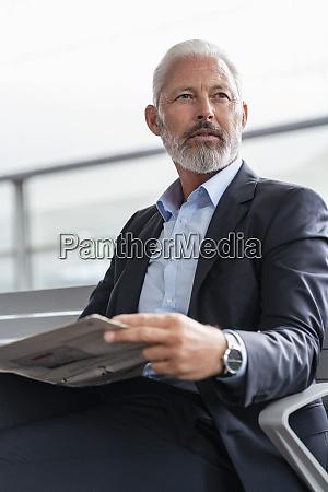 mature businessman sitting in waiting area