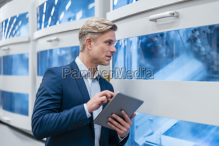 businessman using tablet at a machine