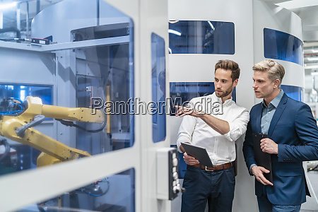 two businessmen talking at robot in