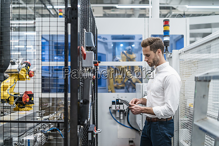 businessman using tablet at a robot