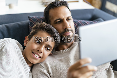 happy father and son using tablet