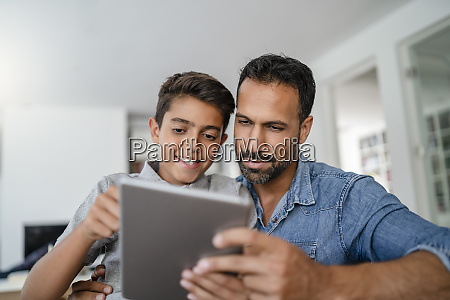 father and son using tablet together