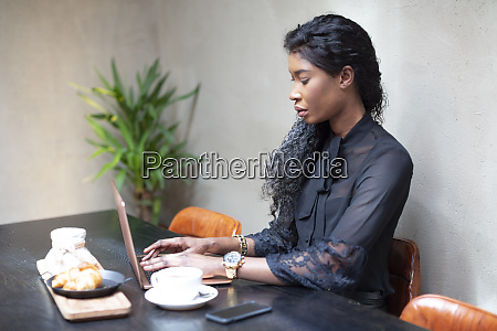 chic businesswoman using laptop at table