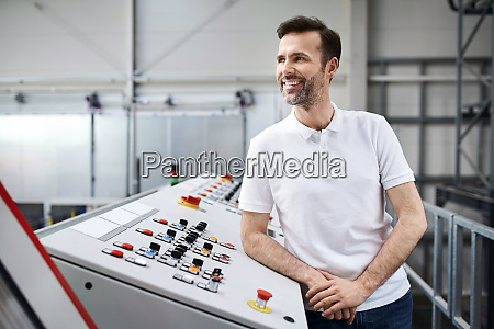 smiling man standing at control panel