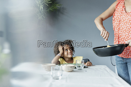 mother serving meal for daughter sitting
