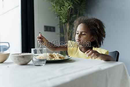 girl eating pasta at dining table