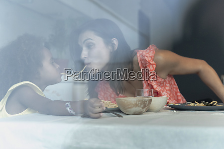 mother and daughter eating pasta at