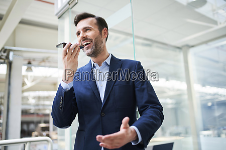 happy businessman using cell phone in