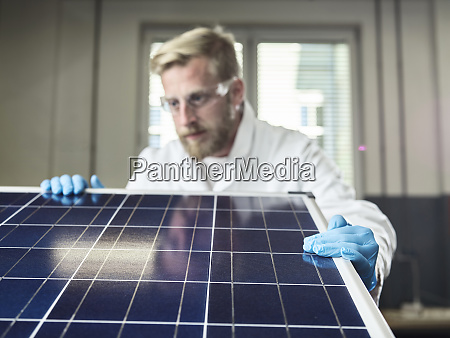technician controlling solar panel in lab