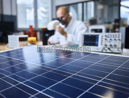 solar panel and technician with microscope