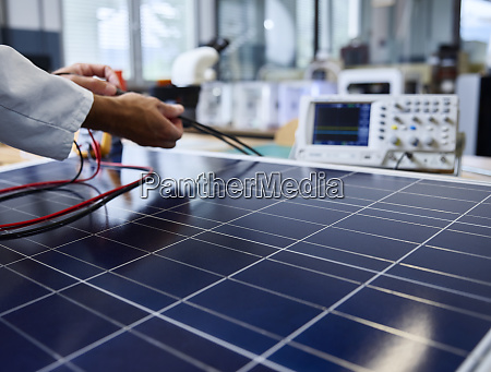 technician controlling cables of solar panel