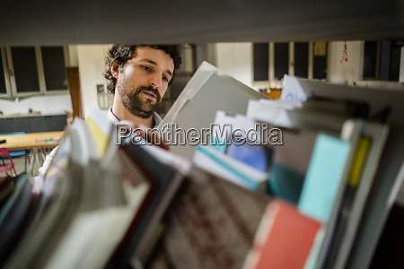 businessman reading file at shelf in