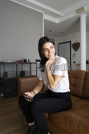 smiling young woman on couch at