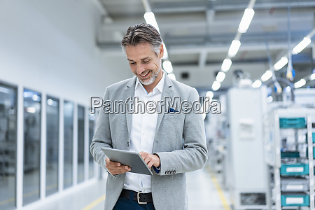 smiling businessman using tablet in a