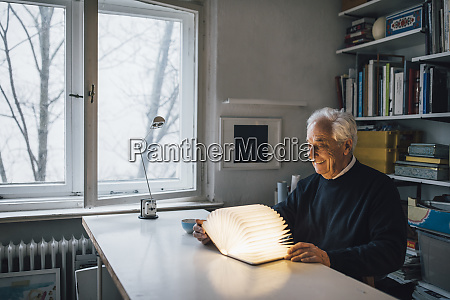 senior man with glowing book on