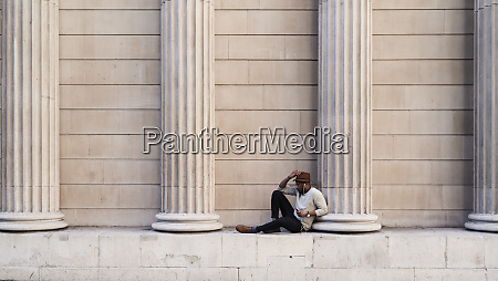 mid adult man sitting between columns
