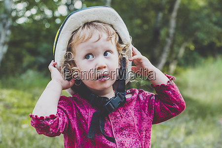 portrait of toddler girl putting on