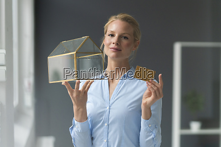 smiling young businesswoman holding glass house