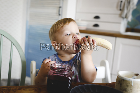 cute little boy eating banana with