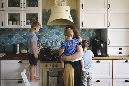 mother cooking with her three sons