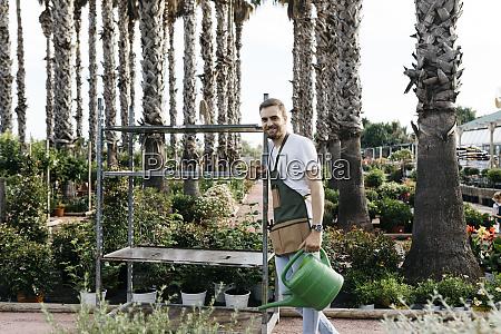 worker in a garden center pushing