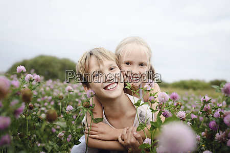 two smiling children on clover field