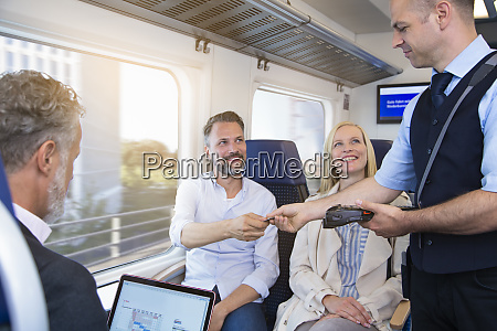 conductor checking tickets of passengers in