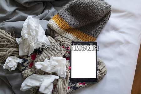 tissues tablet and warm clothes lying