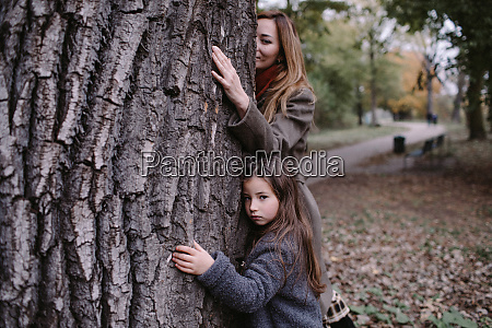 portrait of little girl hugging tree