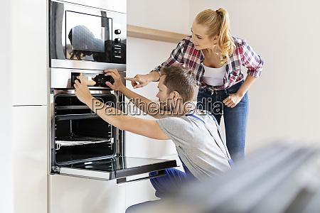 craftsman installing new oven in kitchen