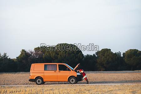 santa claus examining damaged van on