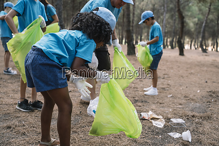 group of volunteering children collecting garbage