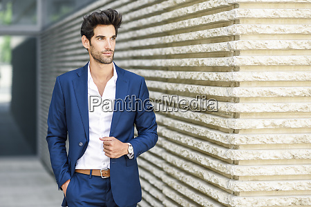 young man wearing blue suit outdoors