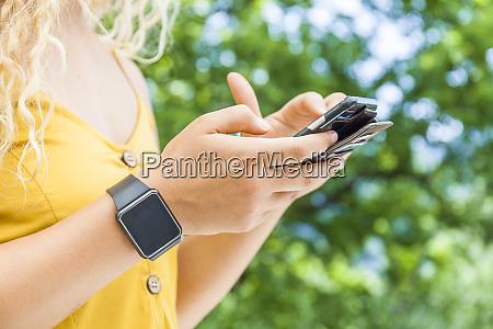 woman using smartphone digital clock