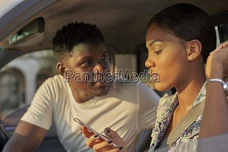 young couple sitting car woman using