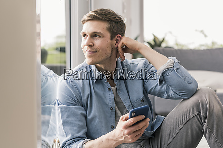 mid adult man sitting by window