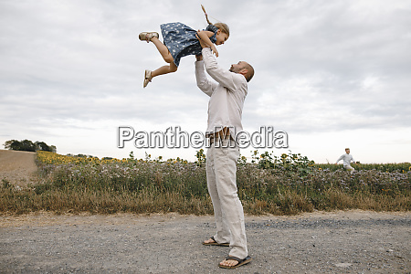 father playing with his daughter holding