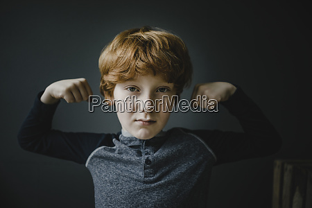 portrait of redheaded boy flexing muscles