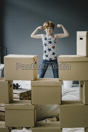 portrait of boy flexing muscles