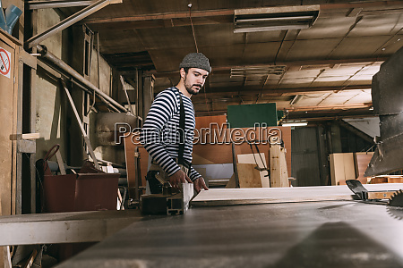 carpenter at work with wooden board