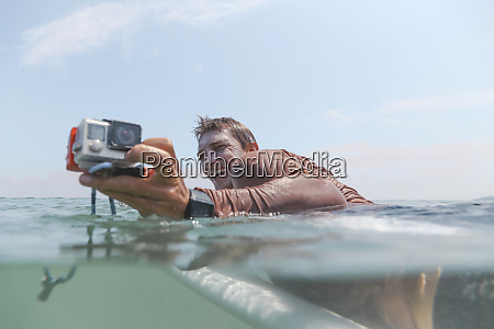surfer with action camera lying on