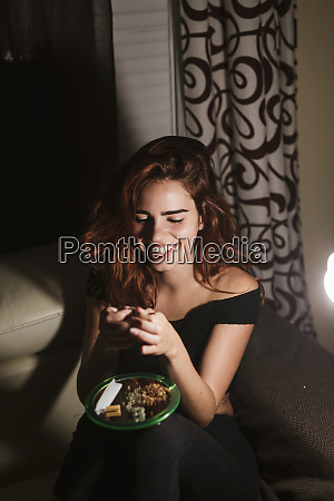 young woman rolling a joint at
